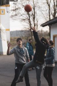 Vier junge Leute, die Basketball spielen, aufgenommen beim Jahrestreffen der TREFFPUNKTE-Gruppen